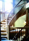 Natural Wood Stairs from upper level to basement level showingcurved handrailing.