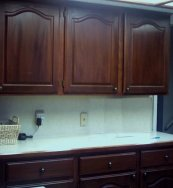 Kitchen cabinets and cupboards refinished in cherry wood color.