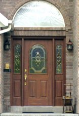 Full view of exterior woodgrained door matching exterior brick of home