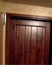 This pictures shows a front view of a real knotty alderwood door with a metal door casing that has been woodgrained to match the door