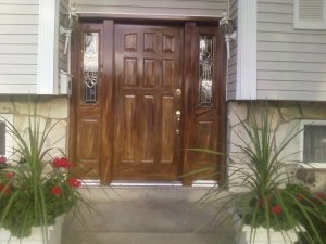 This is a closeup view of a woodgrained exterior metal nine-panel door.