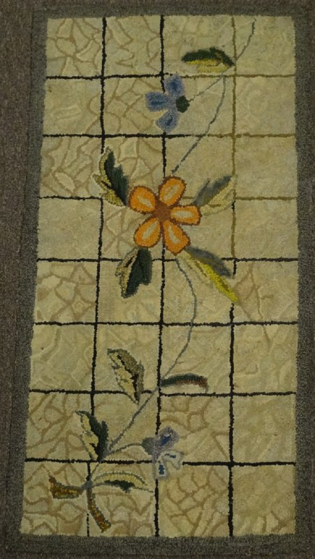A SINGLE FLOWER WITH VINES ANTIQUE HOOKED RUG